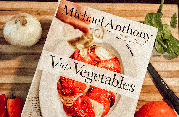 A vegetable cookbook on a cutting board with a knife and fresh vegetables creatively laid out.