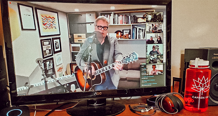 A virtual concert in progress on a computer screen in a home office